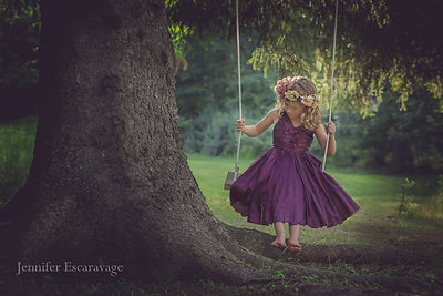young girl in purple dress swinging in a tree