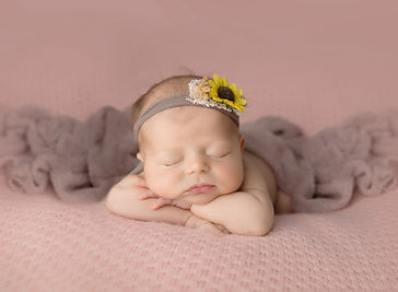 newborn girl with head on hands on pink blanket with sunflower headband