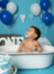 1 year old boy in tub eating cake