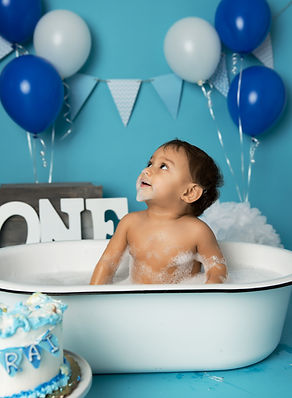 1 year old boy in tub eating cake
