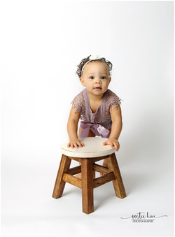 1 year old girl leaning on stool on whit