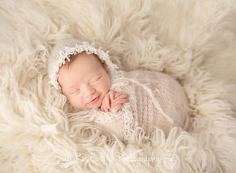 baby girl wrapped on cream fur blanket