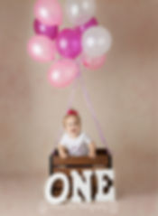 1 year old girl in basket with pink helium balloons