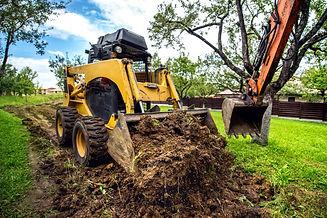 Yellow mini bulldozer working with earth