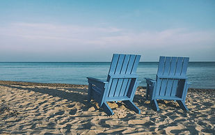 Two Blue Deckchairs On A Sandy Beach