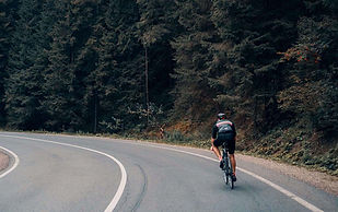 Cyclist In Black Going Round A Corner Surrounded By Large Trees