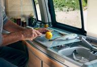 A man slicing a lemon  in a VW California Ocean