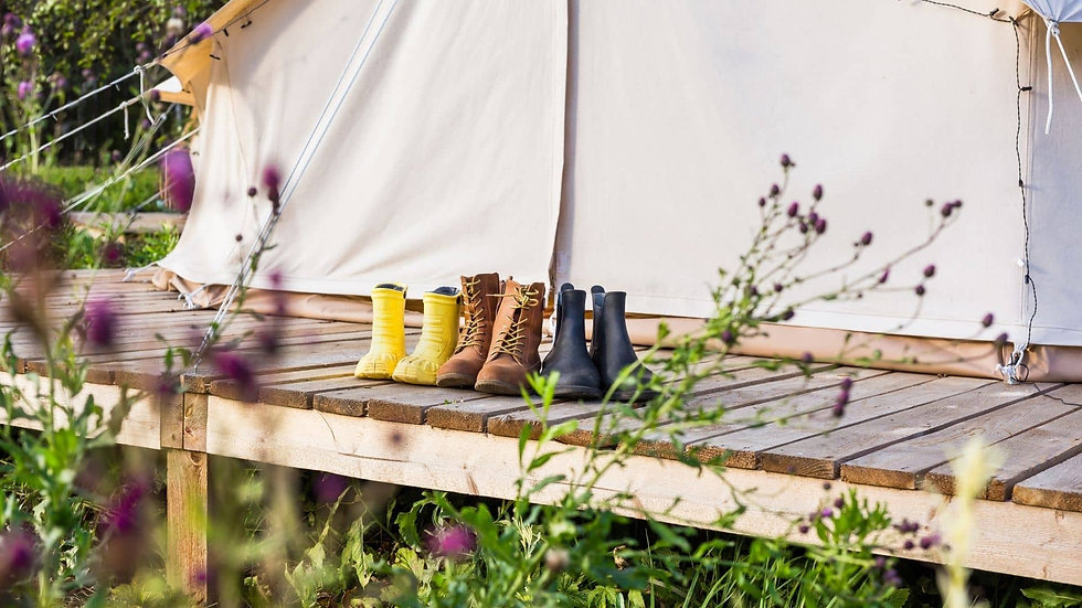 Three pairs of boots on a decking outside of a closed bell tent