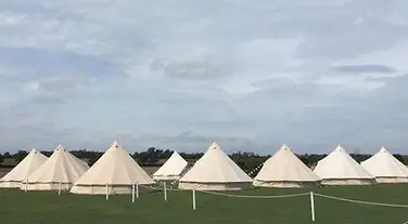 Lots of bell tents in a green field with grey sky