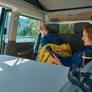 Lady Using Her Phone Resting On A Yellow Coat Inside a VW California Ocean