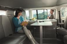 Woman reading a book  in a VW California Ocean while a man looks through the window