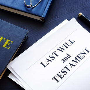 Paper with 'last will and tesament' written on it with blue books around it
