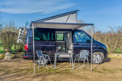 The Awning & Table & Chairs of a VW Camper California Ocean 6.0 Outside