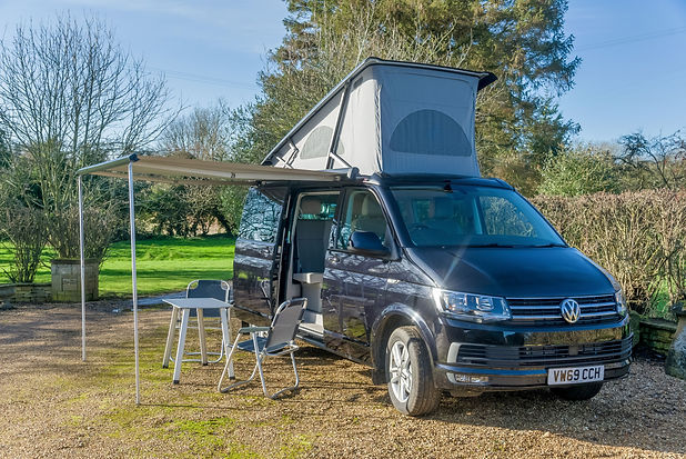 VW Camper California with Awning & Roof Up and Table and Chairs Outside