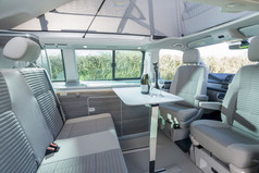 Grey Interior of a VW Camper California Ocean 6.0 with Champagne Glasses and Bottle On Table