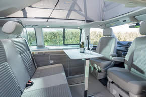 Inside dining area of VW California Camper with Champagne