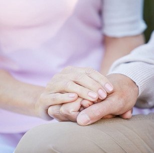 A younger person holding the hand of an older person