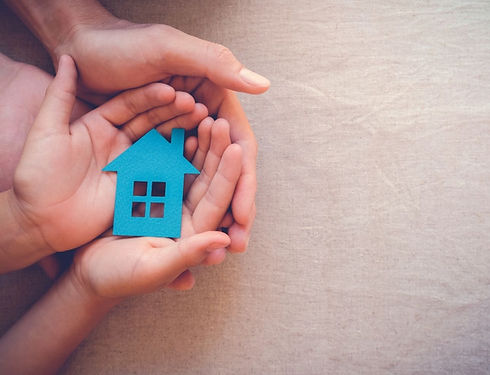 A toddler holding a blue house shape with parent holding their hands
