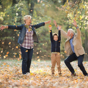 Grandparents playing in the autumn leaves with a child