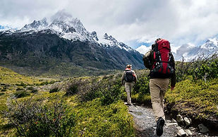 Man and Woman Hiking Near Mountains with Green Scenery