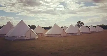 Bell tents in a field with clouds in the sky