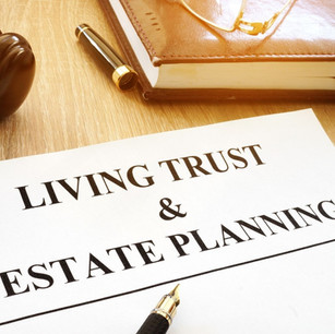 Paper with 'living trust & estate planning' written on it, with a fountain pen on top