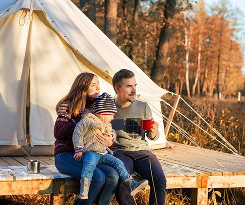 two adults and a baby sat outside a bell tent on decking drinking coffee