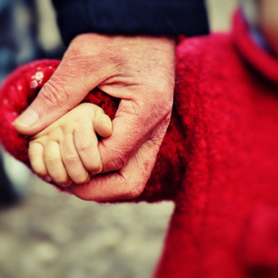 Elderly person holding the hand of a toddler