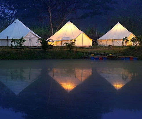 Bell tents next to a lake lit up at night