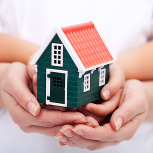 Parents holding hands with toddler while holding a model of a house