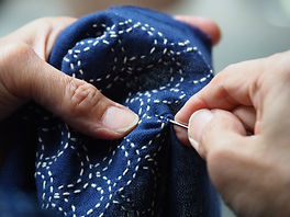 Woman's hands sewing running stitch in b