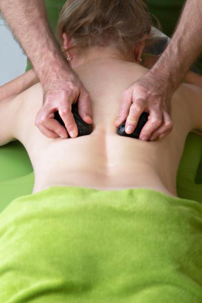 Een hotstonemassage bevordert de bloedcirculatie en helpt spierspanning en pijn te verlichten