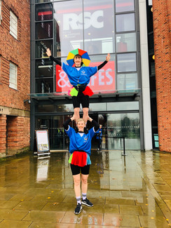 Cat Stood on Jess' shoulders outside the RSC in brightly coloured football kits
