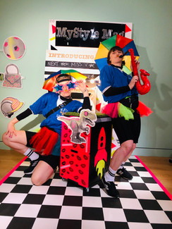 Jess and Cat stood on a checkered dance floor in brightly coloured football kits, posing with a bright orange saxophone and pink star sunglasses.