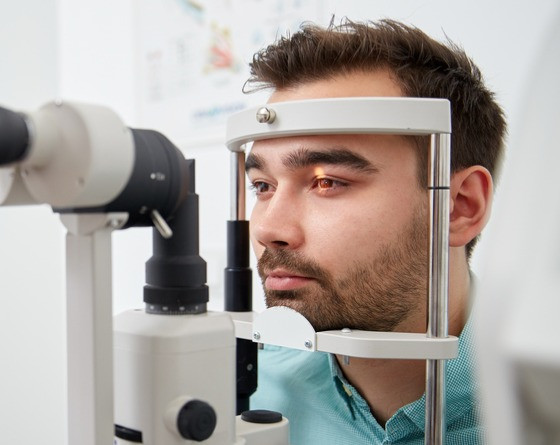 optometrist viewing patient's eyes through slit lamp to detect ocular health problems