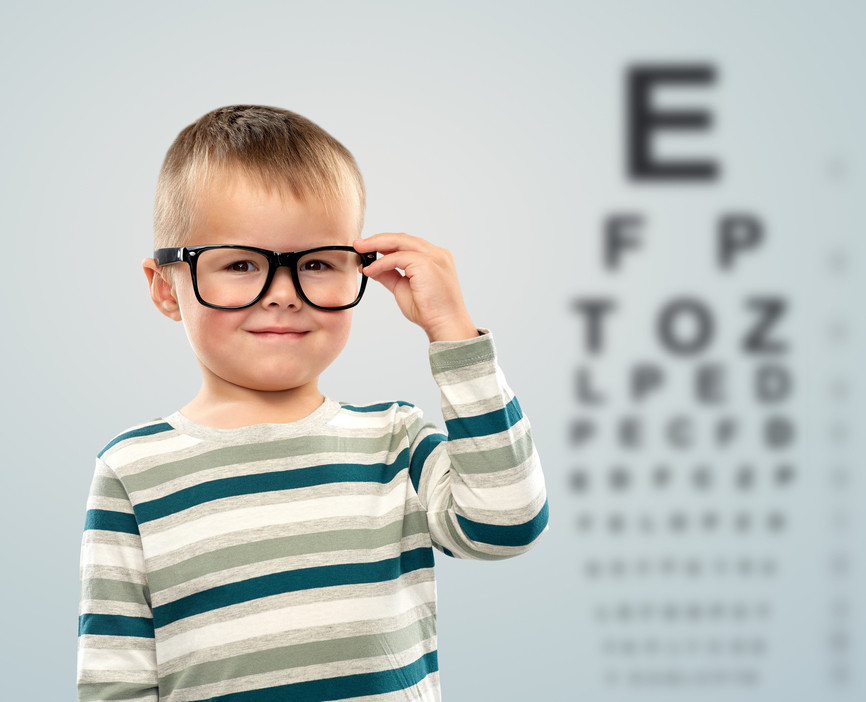 Child wearing eyeglasses after getting eye exam with optometrist.