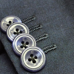 Horn buttons, missing buttons and tight and clean stitching on buttonholes. Above all, the cross sti
