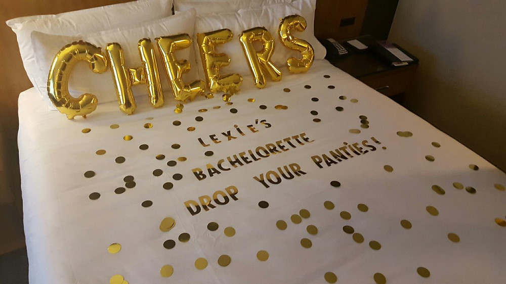 Cheers Balloons and confetti on hotel bed