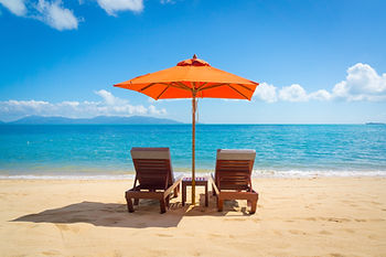 Two lounge chairs with sun umbrella on a