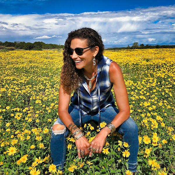 jeweler deborah klezmer in field of daisies in Santa Fe