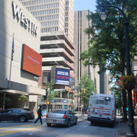Pedestrians, cars, and a MARTA bus mix in the street in front of the Westin hotel.