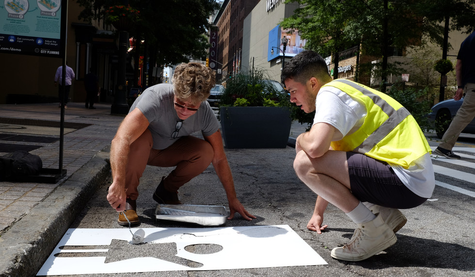 Staff painting stencils in the expanded pedestrian space