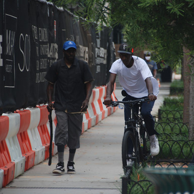 Pedestrian and cyclist on the sidewalk next to the future Winship Cancer Institute, which is currently under construction north of Emory University Hospital Midtown at the corner of Peachtree Street and Linden Avenue.