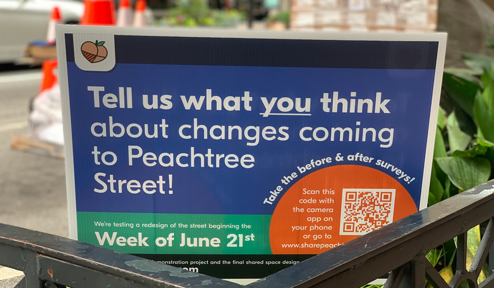 Signs inviting community members to share feedback with an online survey