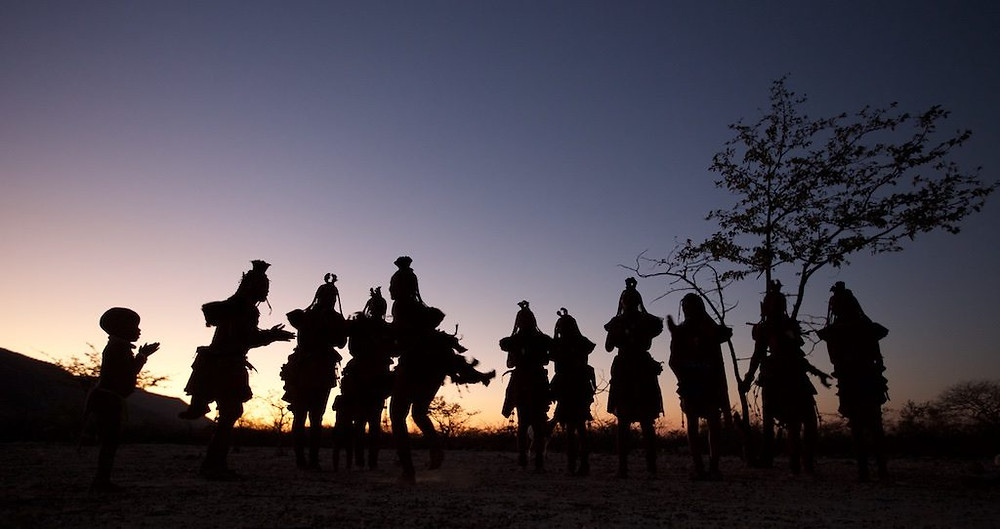 Himba dancers silhouetted by sunset