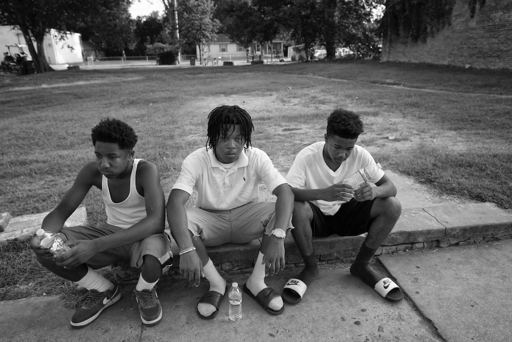 Three young black men sitting on sidewalk