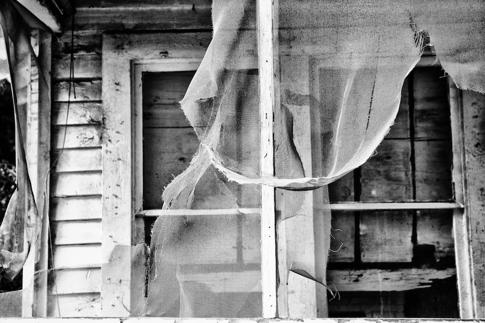 Rotting windows with tattered curtains