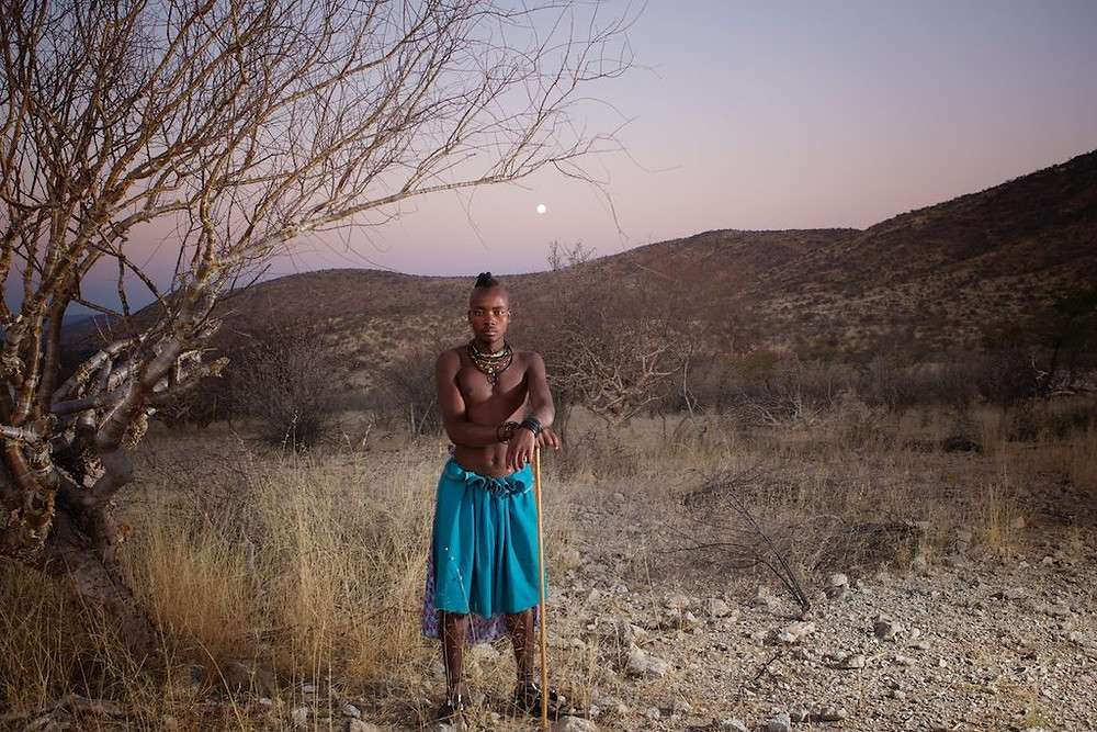 Young Himba man standing near tree