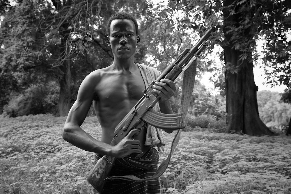 Omo River Valley youth holding rifle