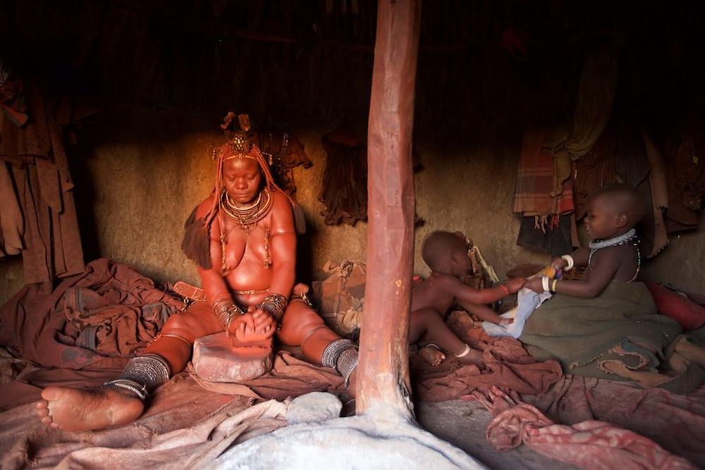 Himba woman grinds grain, children play beside her
